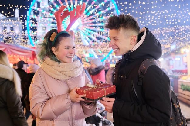Ein paar junge leute auf dem weihnachtsmarkt. glücklicher feiertagsjunge und -mädchen, die geschenkbox geben