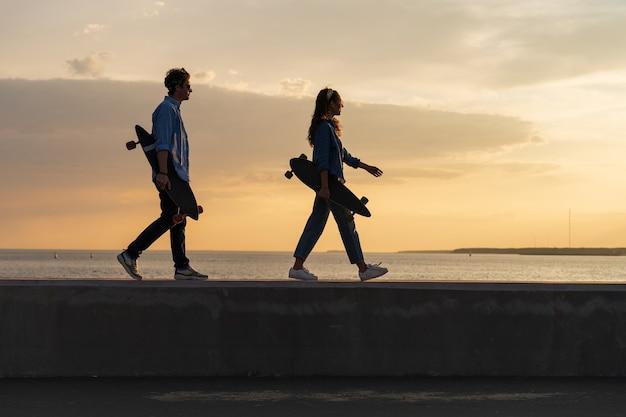 Ein paar junge longboarder laufen am meer mit skate bei sonnenuntergang lifestyle und freiheitskonzept