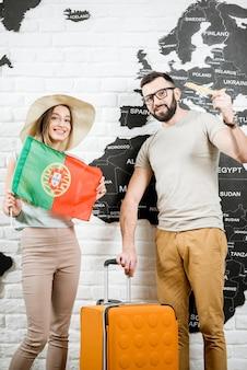 Ein paar junge reisende, die mit portugiesischer flagge in der nähe der wand mit weltkarte stehen und von sommerferien in portugal träumen