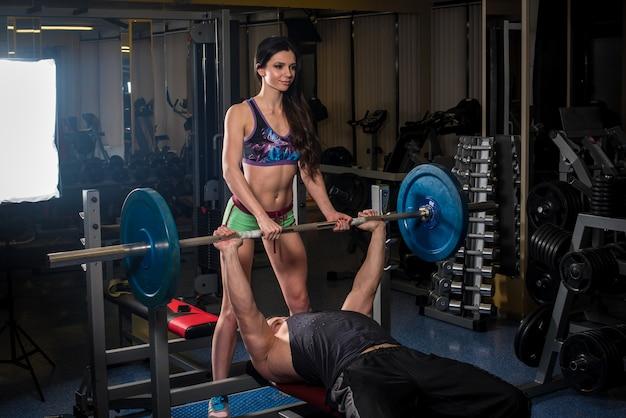 Ein paar junge sportler sind im fitnessstudio beschäftigt und helfen sich gegenseitig. fitness, bodybuilding.