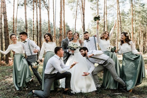 Ein paar jungvermählten in einem kreis enger freunde lachen und haben spaß