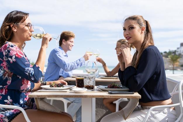 Ein paar lesbische mädchen, die weißwein auf einer terrasse eines restaurants trinken