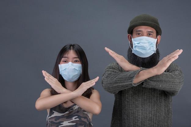 Ein paar liebe trägt maske, während stop hand auf schwarzer wand machen.