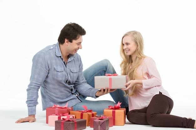 Ein paar liebende sitzt auf dem boden und gibt sich gegenseitig geschenke. ferien.
