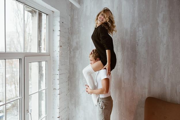 Ein paar liebende, umarmen, küssen, lachen. das mädchen in langem schwarzen pullover und weißem hochgolf. hellgraues interieur, großes fenster, brauner, stilvoller stuhl.