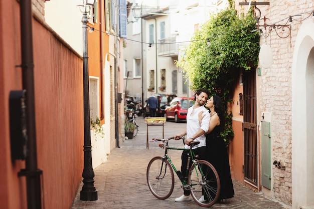 Ein paar liebhaber mit dem fahrrad durch die straßen der altstadt spazieren.