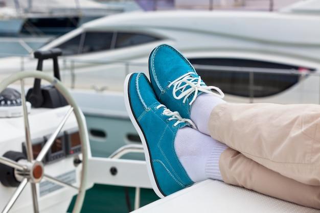 Ein paar menschliche beine in hosen und hellblauen topsidern auf yachtdeckhintergrund. segeln