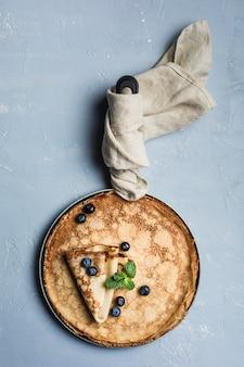 Ein paar pfannkuchen in einer pfanne mit blaubeeren und minze