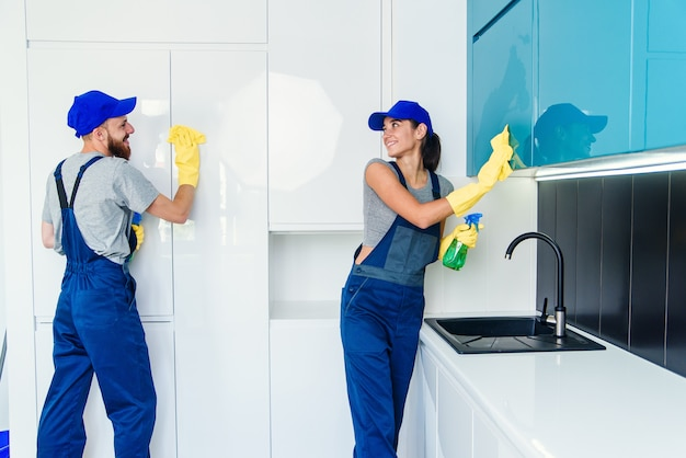Ein paar professionelle reinigungskräfte in blauer uniform reinigen die möbel mit tüchern und spray in der modernen küche.