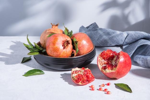 Ein paar reife saftige granatäpfel in einem teller auf grauem hintergrund im morgensonnenlicht. vorderansicht