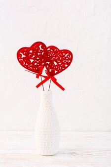 Ein paar rote gelockte herzen in einem weißen vase auf dem tisch verziert durch das stricken
