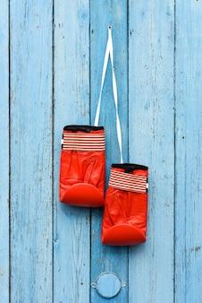 Ein paar rote lederne boxhandschuhe, die an einer weißen schnur hängen