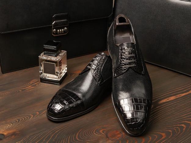 Ein paar schwarze herrenschuhe liegt auf einer oberfläche aus dunklen, geworfenen brettern neben einer flasche parfüm vor dem hintergrund zweier aktentaschen aus leder für männer. seitenansicht. boss-stil