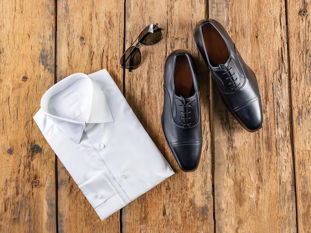 Ein paar schwarze lederschuhe mit weißem hemd und sonnenbrille liegt auf der oberfläche der alten draufsicht auf verlassene bretter