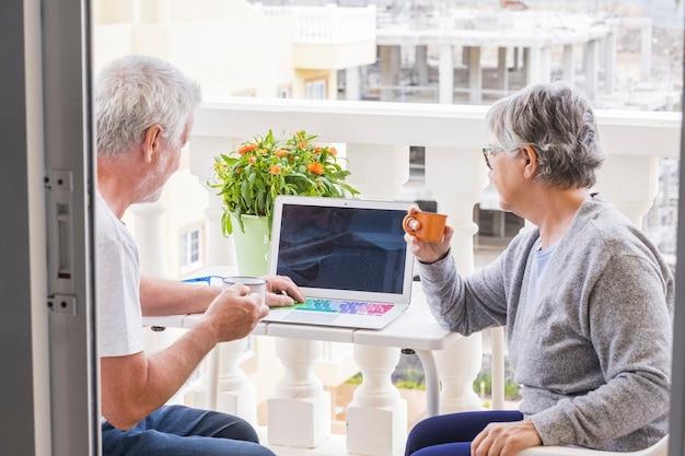 Ein paar senioren auf der terrasse, die spaß haben und genießen - mann mit laptop, der seiner frau etwas zeigt - frau mit kaffee und brille, die den mann ansieht und anlächelt - im freien