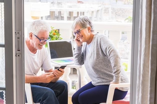 Ein paar senioren, die lächeln und mit kaffee und laptop auf der terrasse auf das telefon schauen - outdoor- und outdoor-lifestyle - heirateten glücklich im ruhestand und genießen diesen moment
