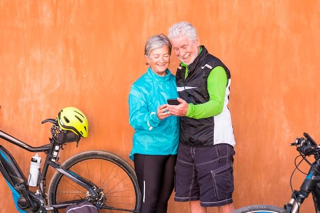 Ein paar senioren, die mit ihren beiden fahrrädern stehen, mit roter und oranger wand im hintergrund - reife zwei personen, die das gleiche telefon benutzen und anschauen