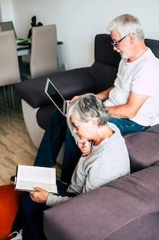 Ein paar senioren lächeln und schauen auf das tablet - frau, die den mann mit liebe auf dem sofa angreift - drinnen - zeigt