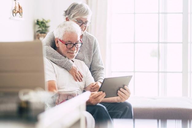 Ein paar senioren lächeln und schauen auf das tablet - frau, die den mann mit liebe auf dem sofa in beschlag nimmt - drinnen