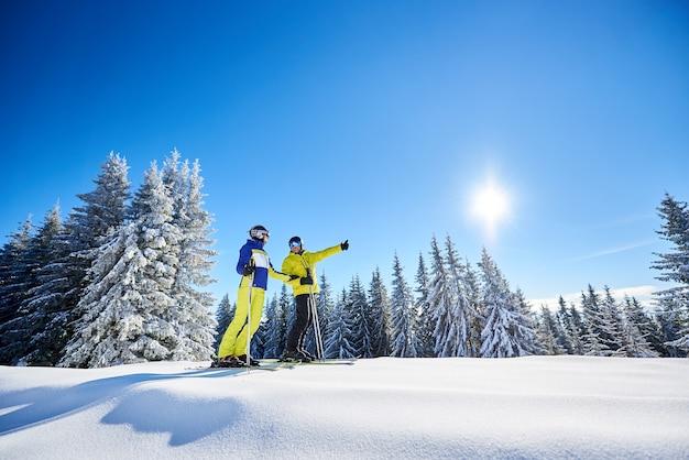 Ein paar skifahrer auf skiern auf dem hügel im skigebiet. freizeitaktivitäten im bergkonzept. low-winkel-aufnahme in voller länge