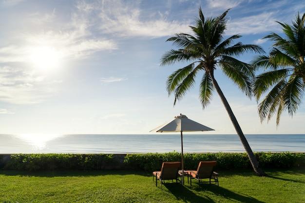 Ein paar strandstühle auf grünem gras mit großer palme am schönen blauen himmel des sonnenaufgangs setzen auf den strand