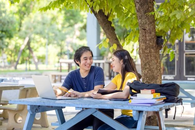 Ein paar studenten, die in einer universität im freien sitzen und einen laptop benutzen, um online zu recherchieren