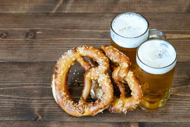 Ein paar tassen mit hellem bier und brezeln auf holz