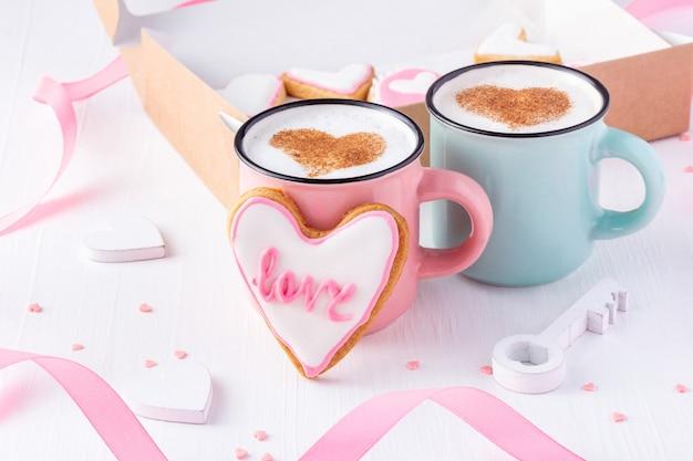 Ein paar tassen mit latte herzförmigen keksen, die mit wortliebe für valentinstag glasiert werden