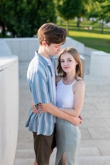 Ein paar teenager, die händchen halten und sich im park umarmen die erste liebe