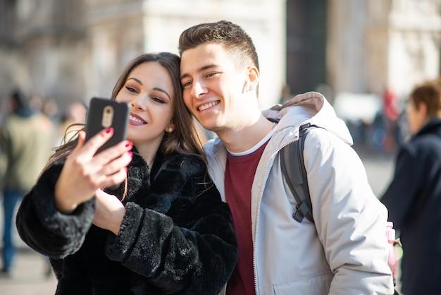 Ein paar touristen, die ein selfie in einer europäischen stadt machen