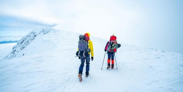 Ein paar touristen, die mit schnee bedeckten winterberggipfel trekken
