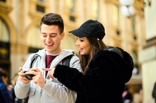 Ein paar touristen, die sich die bilder ansehen, die auf ihrer reise aufgenommen wurden