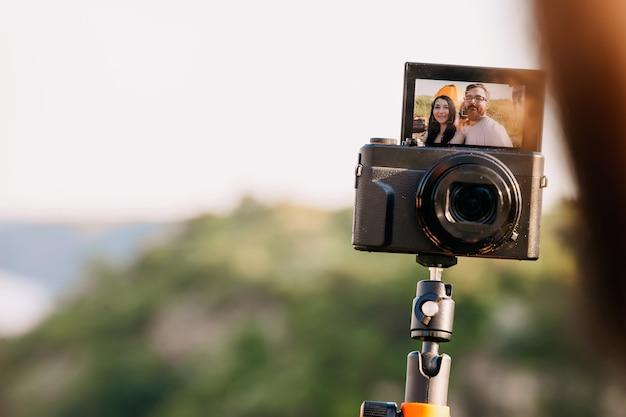 Ein paar touristen filmen vlog im freien.