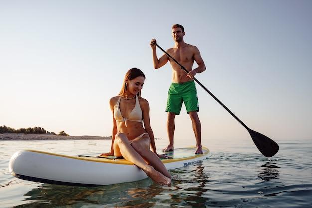 Ein paar touristen, junger mann und frau, die spaß beim paddeln auf see haben?