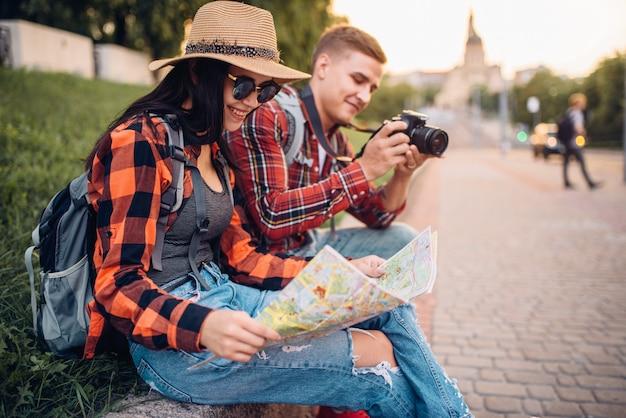 Ein paar touristen studieren die karte der sehenswürdigkeiten