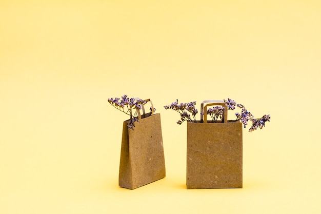 Ein paar umweltfreundliche einkaufstüten aus kraftpapier und trockenblumen darin auf gelbem hintergrund. verkauf von geschenken zum schwarzen freitag