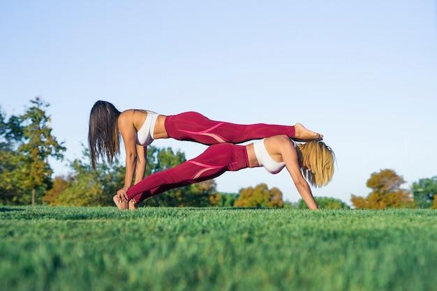 Ein paar von zwei frauen, eine junge frau und eine andere ältere frau, machen im freien dehn- und yogaübungen mit akrobatischen figuren, eine ist ein persönlicher trainer und sie tragen sportkleidung