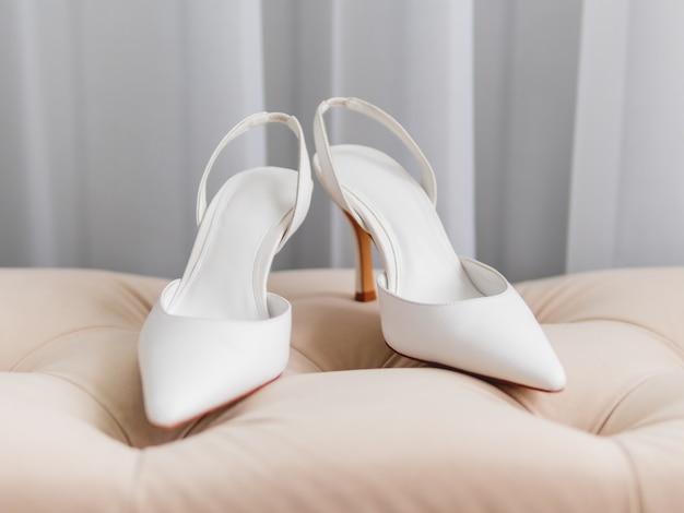 Ein paar weiße schuhe, allgemein d'orsay genannt, auf beigem stuhl.