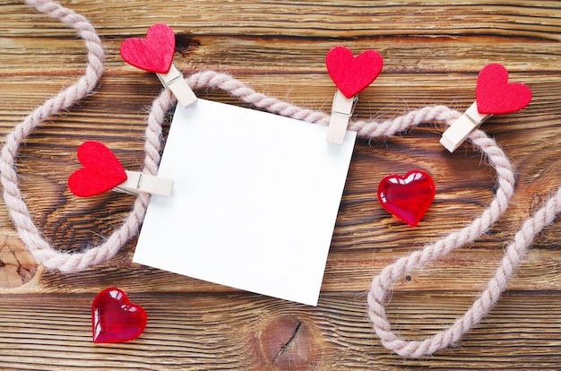 Ein papier befestigt mit wäscheklammern zum seil und zu den süßigkeiten in form der herzen auf einem holztisch.