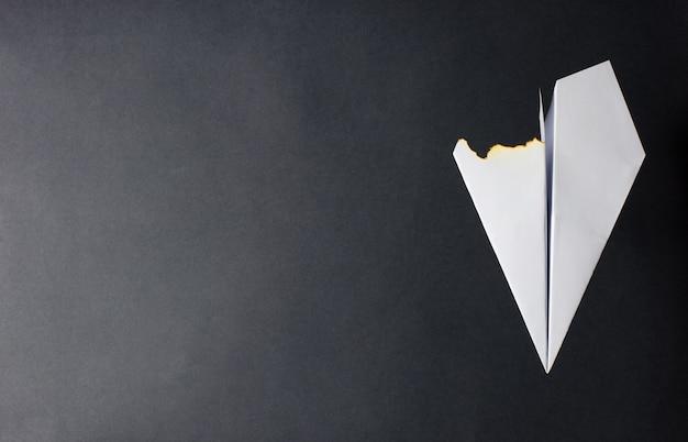 Ein papierflugzeug mit einem verbrannten flügel. dunkler hintergrund. das konzept eines feuers im flugzeug oder des absturzes.