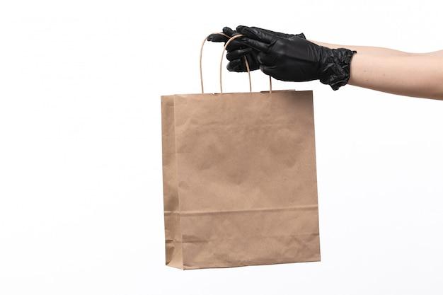 Ein papierpaket mit vorderansicht, das von schwarzen handschuhen auf weiß leer gehalten wird