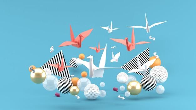 Ein papiervogel unter bunten kugeln auf einem blauen raum