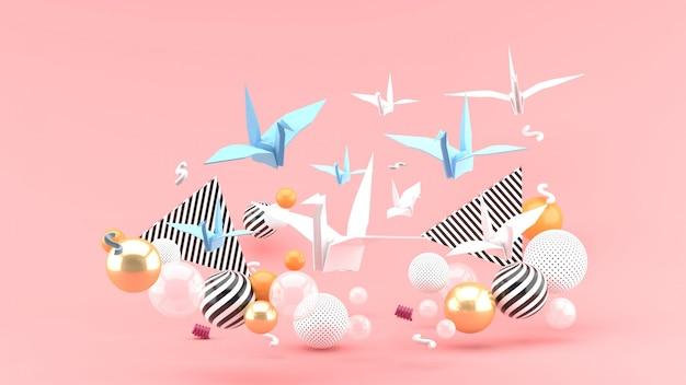 Ein papiervogel unter bunten kugeln auf einem rosa raum