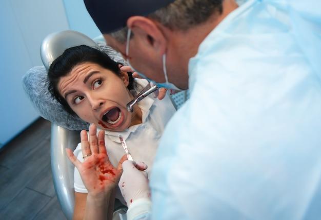 Ein patient in einem zahnarztstuhl sieht einen arzt verängstigt an, der blutzahnwerkzeuge in seinen händen hält. horrorkonzept in der zahnmedizin. halloween
