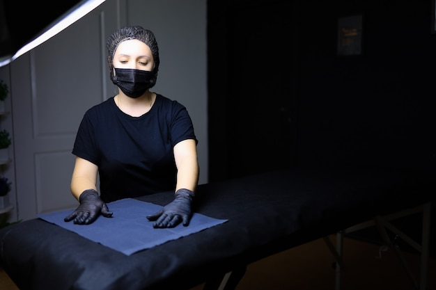 Ein permanent make-up artist in schwarzer uniform steht vor einer couch im kosmetikraum