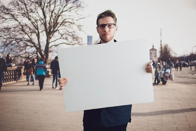 Ein personenaktivist, der einen kopierraum aus pappe hält, ein vorlagenmodell für text