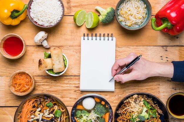 Ein personenschreiben auf dem notizblock mit stift und traditionellem thailändischem lebensmittel auf holztisch