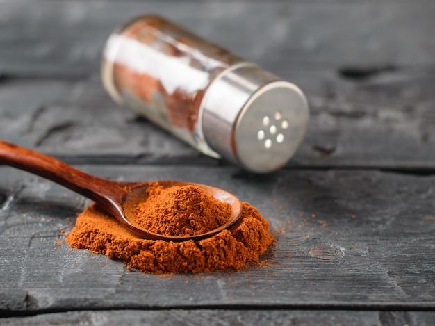 Ein pfefferglas und ein löffel gemahlener chili auf einem rustikalen tisch