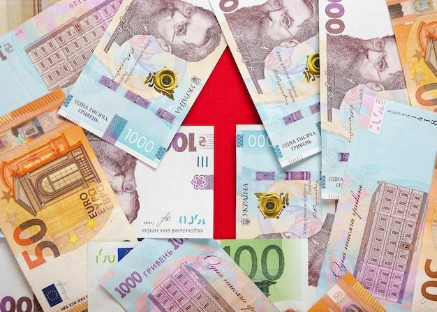 Ein pfeil mit banknoten von ukrainischen griwna und euro 3