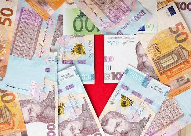 Ein pfeil mit banknoten von ukrainischen griwna und euro 6